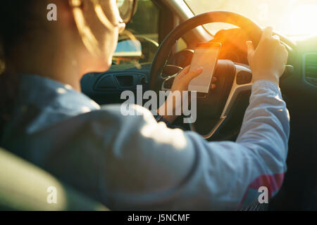 Woman uses a navigator in a smartphone while driving a car - Stock Photo