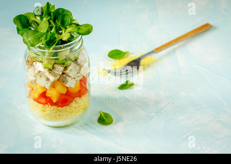 Vegan salad with couscous, tofu and vegetables in a jar. Love for a healthy vegan food concept - Stock Photo