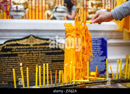 Hand with candle in Wat Doi Suthep Buddhist Temple in Ciang Mai, Thailand - Stock Photo