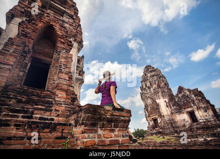Woman in hat looking at ancient ruined Temple of city Lopburi, Thailand - Stock Photo