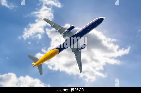 Passenger jet aeroplane flying low under clouds. Underside of plane. Aircraft underside. Plane travel concept. Air - Stock Photo