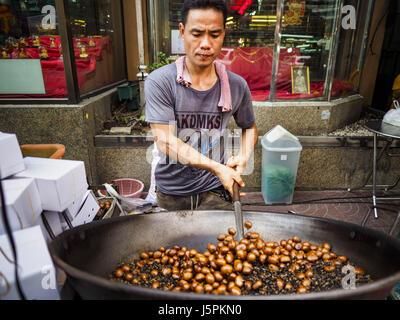 May 18, 2017 - Bangkok, Bangkok, Thailand - A man roasts chestnuts on Yaowarat Road in Bangkok. City officials in - Stock Photo