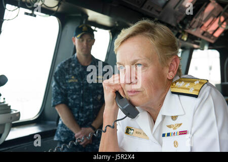U.S. Navy Commander Nora Tyson addresses sailors through the announcing system aboard the USN Independence-class - Stock Photo
