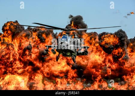A U.S. Army AH-64D Apache attack helicopter flies in front of a wall of fire during the South Carolina National Guard Air and Ground Expo at the McEntire Joint National Guard Base May 6, 2017 in Hopkins, South Carolina.    (photo by Jorge Intriago /US Airforce Photo via Planetpix) Stock Photo