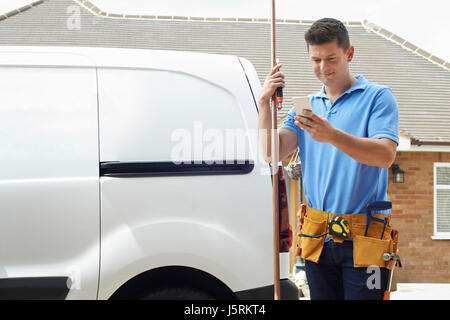 Plumber With Van Using Mobile Phone Outside House - Stock Photo