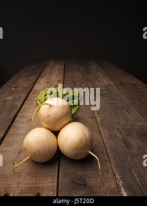 May turnip on a rustic wooden table with space for text - Stock Photo