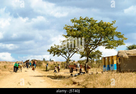 A dirt road passing through a rural village in Malawi, Africa showing an ox cart men pushing bicycles and women - Stock Photo
