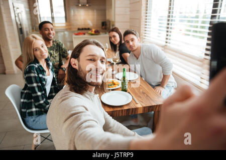 Attractive young man taking a selfie photo with friends in the kitchen while having lunch together at home - Stock Photo