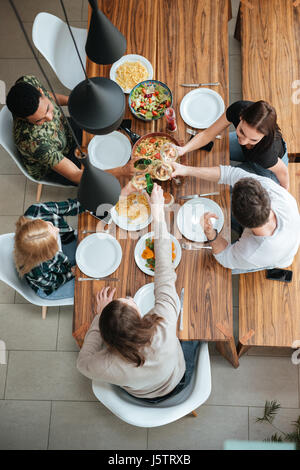 Top view of five people cheering with wine while sitting at the rustic dining table - Stock Photo