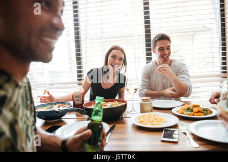 Group of multiracial young friends enjoying meal while sitting at the dinning table on the kitchen together - Stock Photo