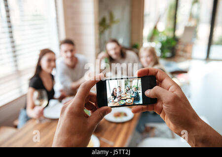 Closeup of man taking pictures of his friends with cell phone eating at the table at home - Stock Photo