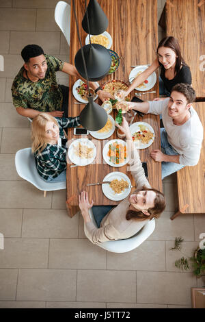 Top view of five people cheering with wine while sitting at the rustic dining table and looking up at camera - Stock Photo