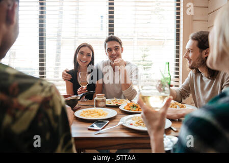 Happy young couple having dinner and talking with friends on the kitchen at home - Stock Photo