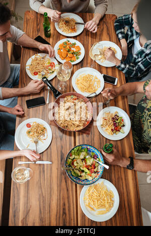 Top view of group of people having dinner together while sitting at the rustic wooden table at home - Stock Photo