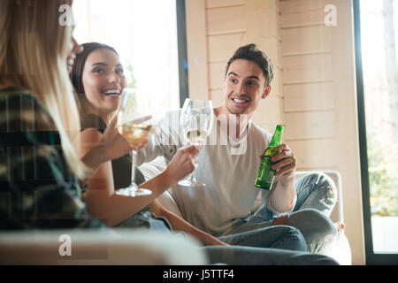 Group of cheerful young friends drinking wine and beer on sofa at home - Stock Photo