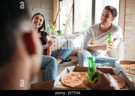 Happy young couple eating pizza, drinking beer and wine with friends at home