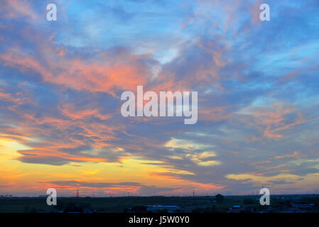 Dramatic sunset over city in spring time - Stock Photo