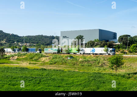 Semi trailers parked outside the central logistics warehouse for the retail company Bershka in Catalonia, Spain. - Stock Photo
