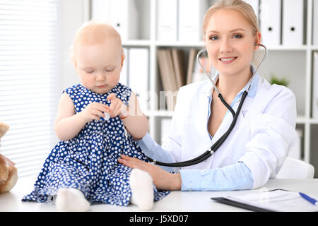 Pediatrician is taking care of baby in hospital. Little girl is being examine by doctor with stethoscope - Stock Photo