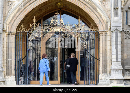 Visitors enter the main door at the west facade of the medieval christian cathedral at Peterborough, England. - Stock Photo