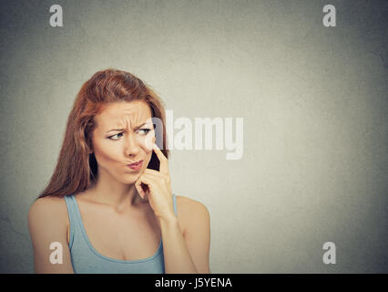 Headshot thoughtful skeptical suspicious young woman on grey background