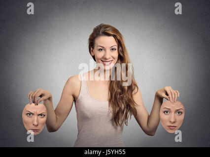portrait beautiful happy girl holds two masks isolated grey wall background. Human face expressions, emotions, feelings, - Stock Photo