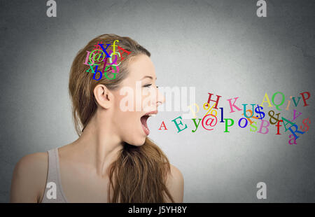 Side view portrait woman talking with alphabet letters in her head and coming out of her open mouth isolated grey - Stock Photo