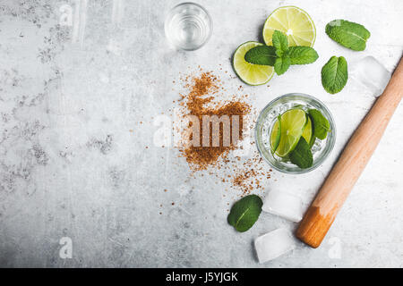 Mojito cocktail ingredients on light gray background. Lime slices, brown sugar, wooden squeezer, rum and mint leaves - Stock Photo