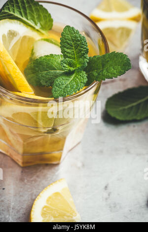 Homemade iced lemon sweet tea with mint on light gray table, delicious refreshment summer drink - Stock Photo