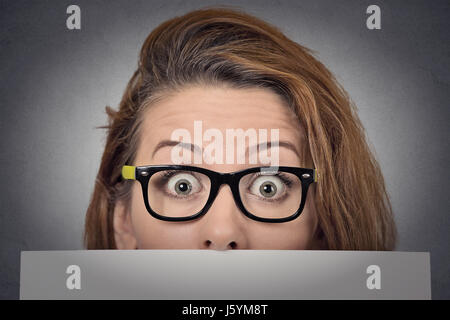 Banner sign woman peeking over edge of blank empty paper billboard. Beautiful young woman with glasses looking surprised - Stock Photo