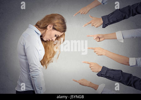 Concept of accusation of guilty businesswoman. Side profile portrait sad upset woman looking down many fingers pointing - Stock Photo