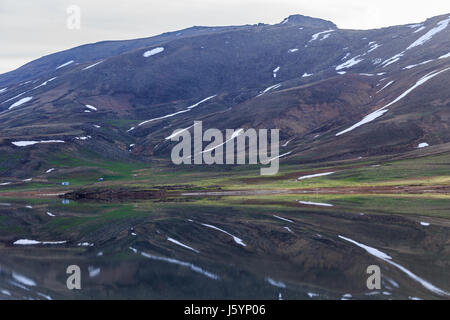 Reflection concept. Horizontal landscape with mountain lake and melting snow reflected in water - Stock Photo