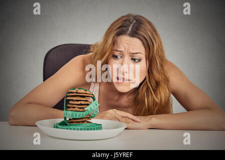 Young fat woman worried measuring her waist Stock Photo Royalty