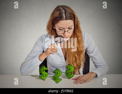 penny pincher. Business woman looking through magnifying glass dollar signs symbol on table isolated grey wall office - Stock Photo