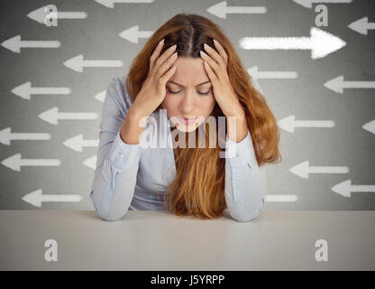 Thoughtful woman taking a chance going against flow. Thoughtful businesswoman sitting at table isolated on grey - Stock Photo