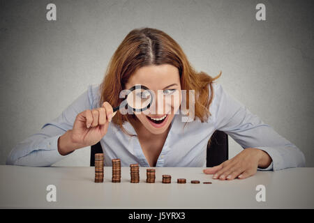 Closeup portrait excited greedy business woman wall street executive looking at growing stack of coins through magnifying - Stock Photo