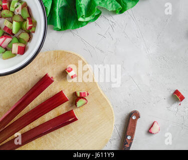 Fresh organic rhubarb stems on wooden cutting board over grey concrete stone background - Stock Photo