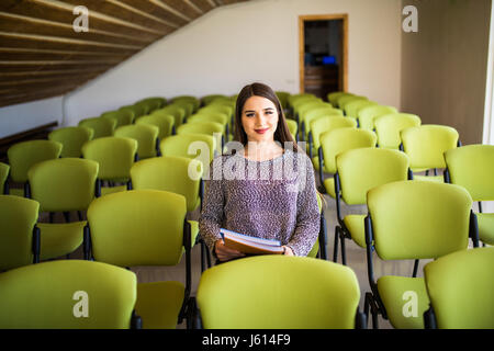 A beautiful business woman sitting alone in an auditorium - Stock Photo