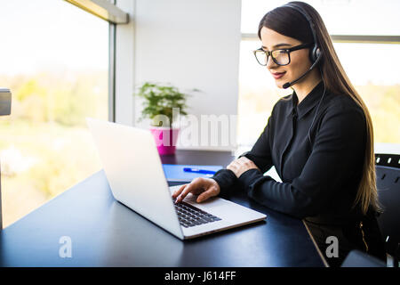picture of smiling female helpline operator with headphones - Stock Photo
