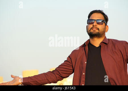 Young Indian man with goggles and outstretched hands as a welcome gesture - Stock Photo