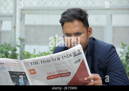 Young Indian corporate man in suit with Bluetooth speaker reading a newspaper - Stock Photo