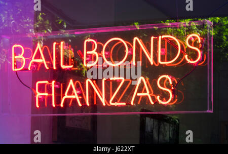 Colorful neon sign in both English and Spanish in the window of a bail bonds company near the Manhattan courts in - Stock Photo