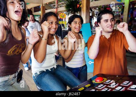 Indiana Valparaiso Zao Island Entertainment Center video game arcade girl boy teen Hispanic fun entertainment reaction - Stock Photo