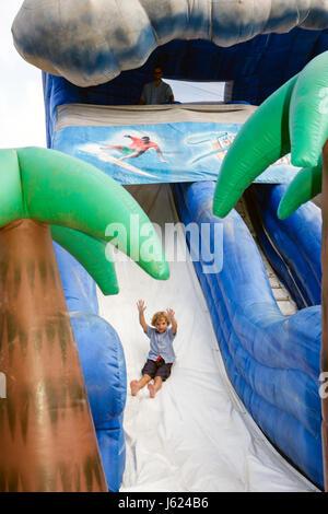 Indiana Valparaiso Zao Island Entertainment Center boy child inflatable slide fun play happy raised arms - Stock Photo