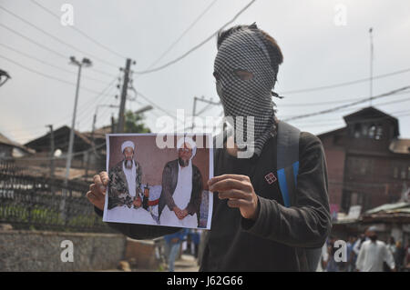 Srinagar, Kashmir. 19th May, 2017. A kashmiri masked protester holds the picture of Majahideens during clashes at - Stock Photo