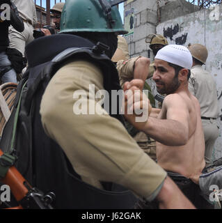 Srinagar, Kashmir. 19th May, 2017. A CRPF trooper beating a protester after being arrested at jamia masjid area - Stock Photo
