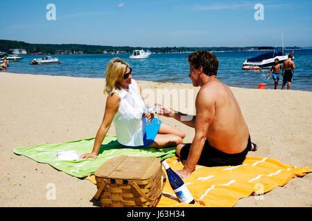 Michigan Traverse City West Arm Grand Traverse Bay Clinch Park beach sand picnic blonde woman man couple romantic - Stock Photo