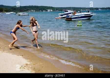 Michigan Traverse City West Arm Grand Traverse Bay Clinch Park three girls teen bikini shoreline play push into - Stock Photo