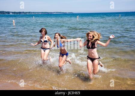 Michigan Traverse City West Arm Grand Traverse Bay Clinch Park three girls teen bikini splash water beach fun recreation - Stock Photo
