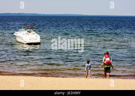 Michigan Traverse City West Arm Grand Traverse Bay Clinch Park man boy girl parent child water beach piggyback play - Stock Photo